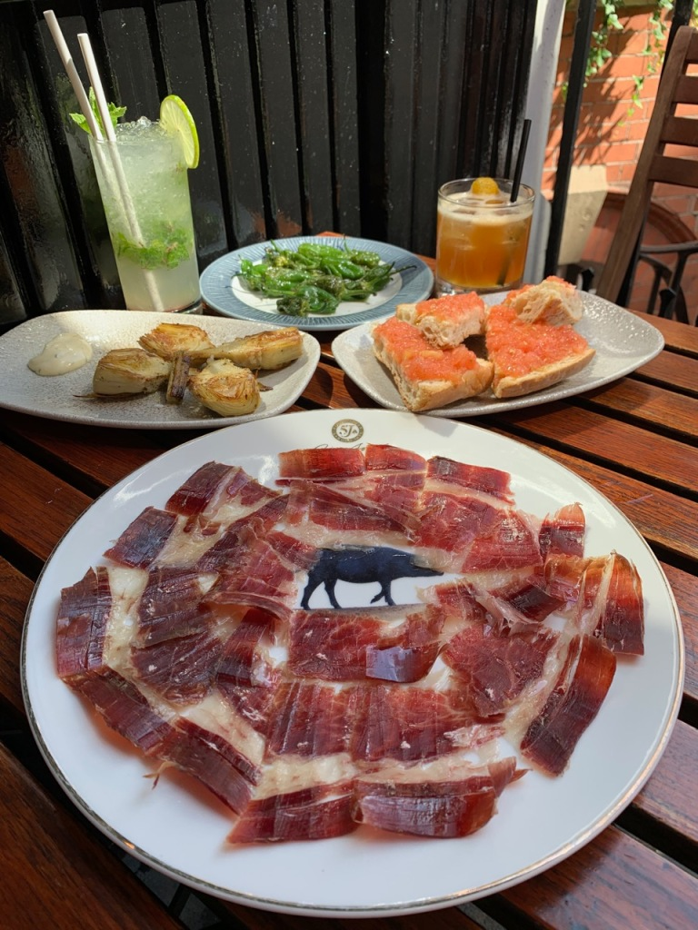 table showing various Spanish tapas including iberico ham, padron potatoes and pan con tomate