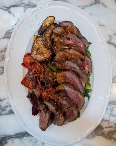 Platter of sliced steak with roasted vegetables