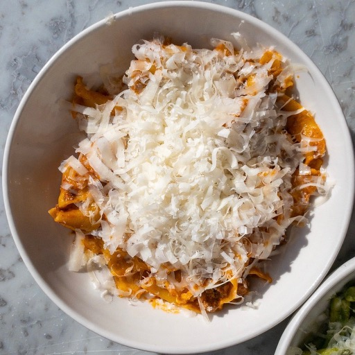 bowl with pasta and covered with cheese shavings