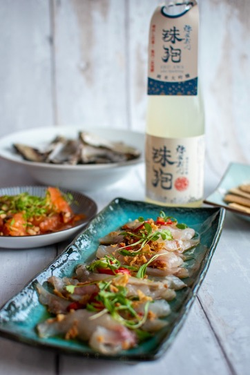 Sea bream ceviche with sake bottle and some other seafood dishes and oysters in the background