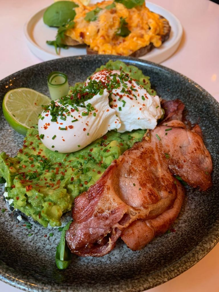 dish with bacon, smashed avocado, poached egg, lime  - garnished with chives and chilli