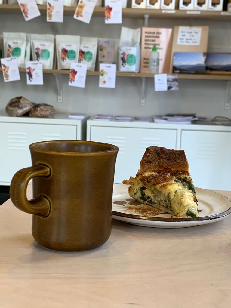 A mug of coffee and a quiche; coffee bags in the background to buy