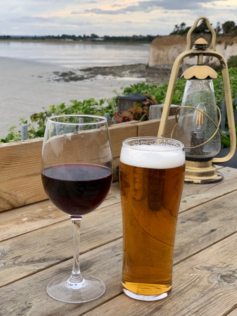 photo showing a glass of wine and a pint with sea and cliffs in the background