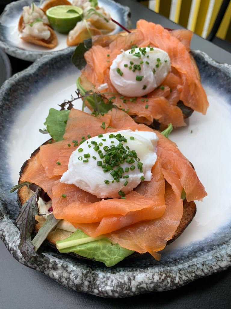 Dish with two bagels, smoked salmon and poached eggs garnished with chives