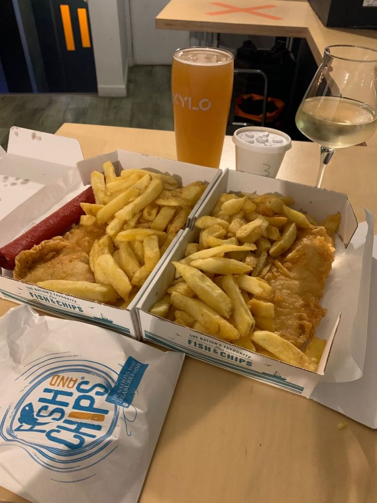 Two portions of fish and chips with beer and wine in the background.