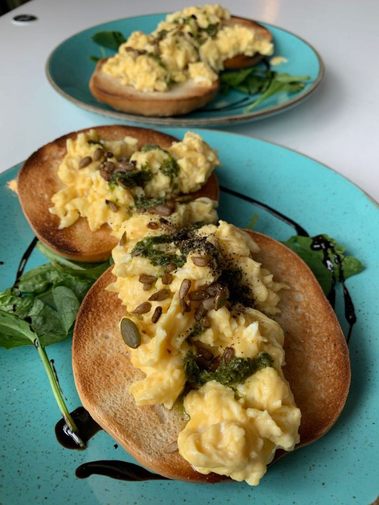 Greenish blue plate with two bagels topped with creamy scrambled eggs, homemade salsa verde & toasted seeds on a bed of leafy greens