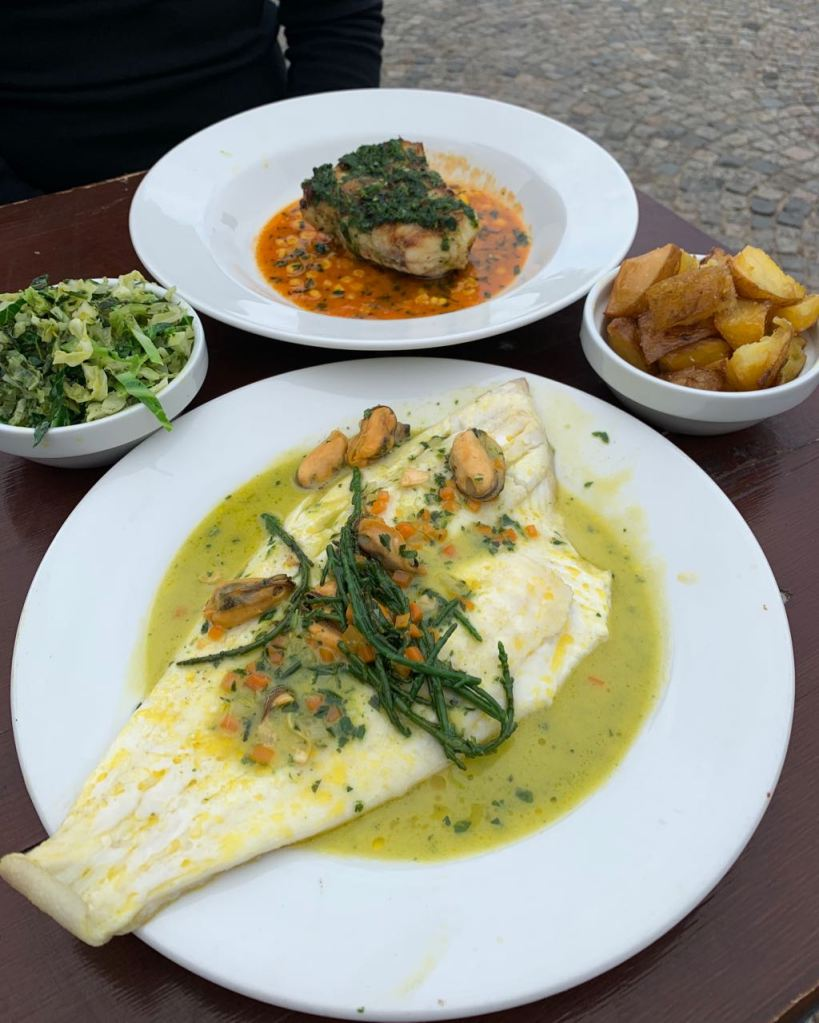 Different plates of food on table with Plaice, Clams, Samphire and Monkfish, Sweetcorn, Paprika Butter