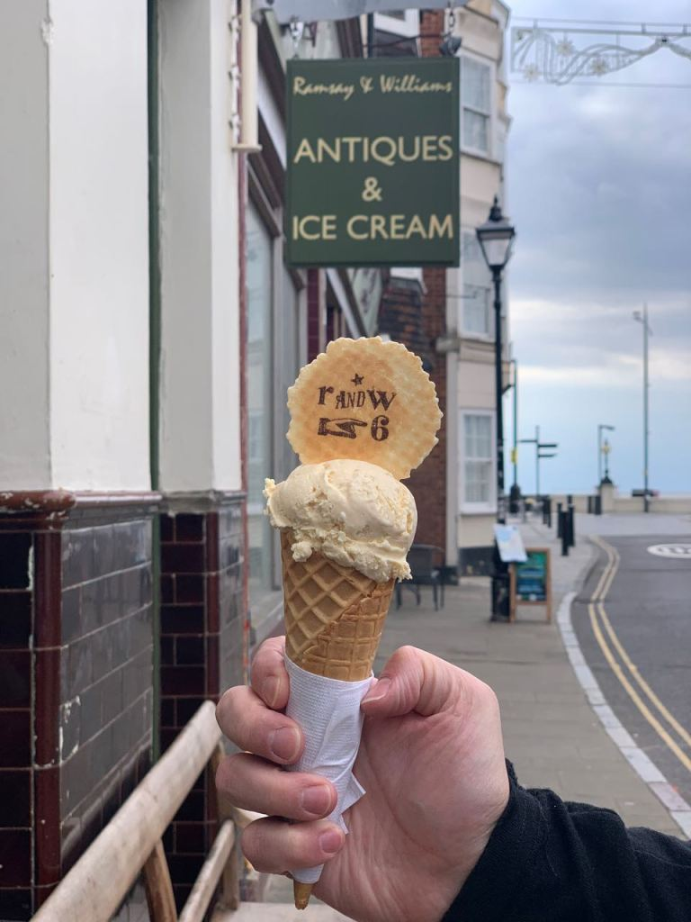 Man holding ice cream cone with Ramsay and Williams sign board in the background saying antiques and icecream