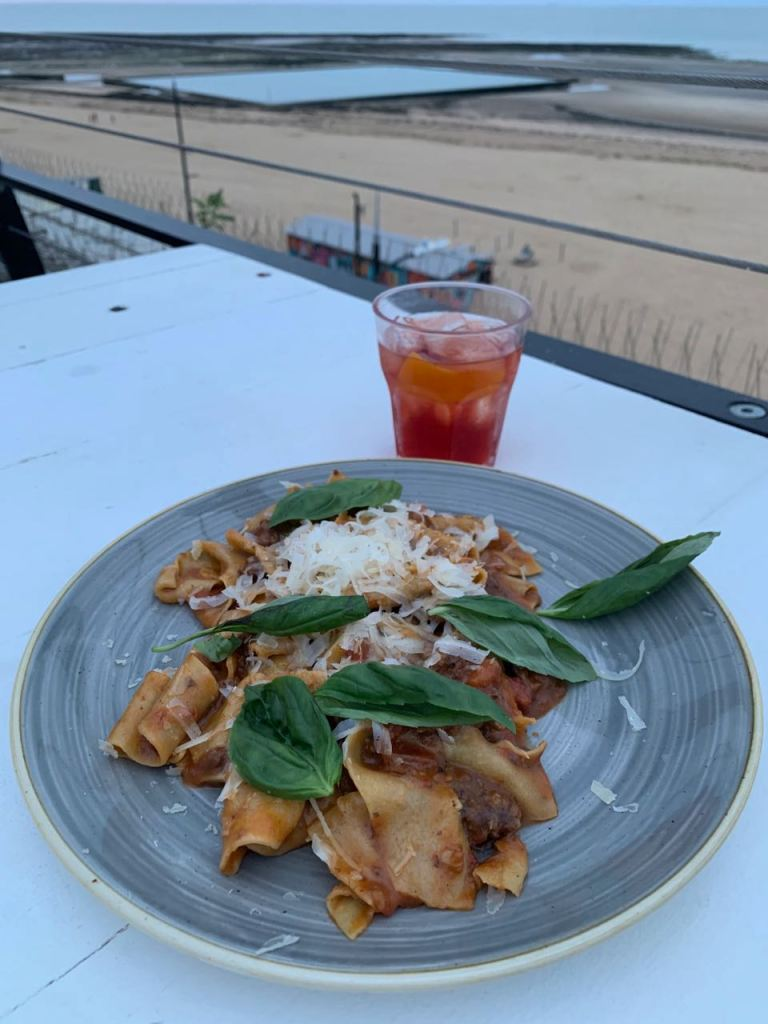 A plate of pasta and a negroni; Margate beach in the background.