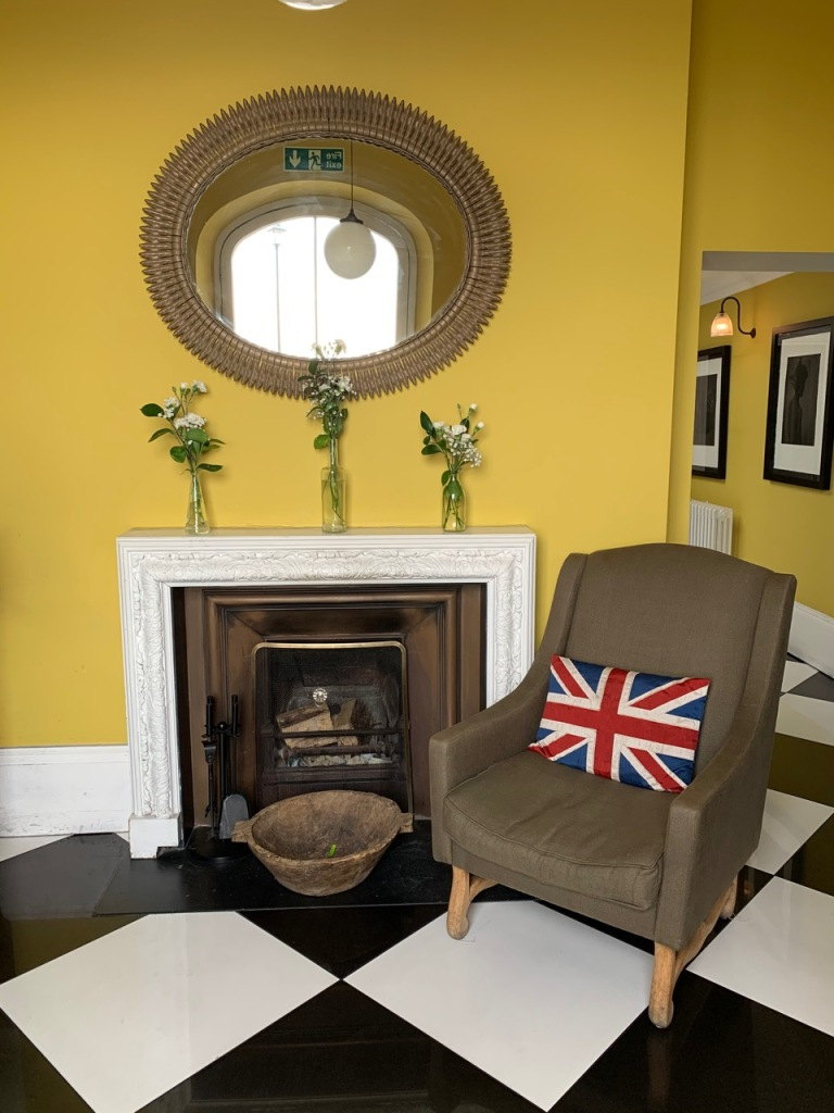 hotel lobby showing fireplace and an armchair against a yellow wall