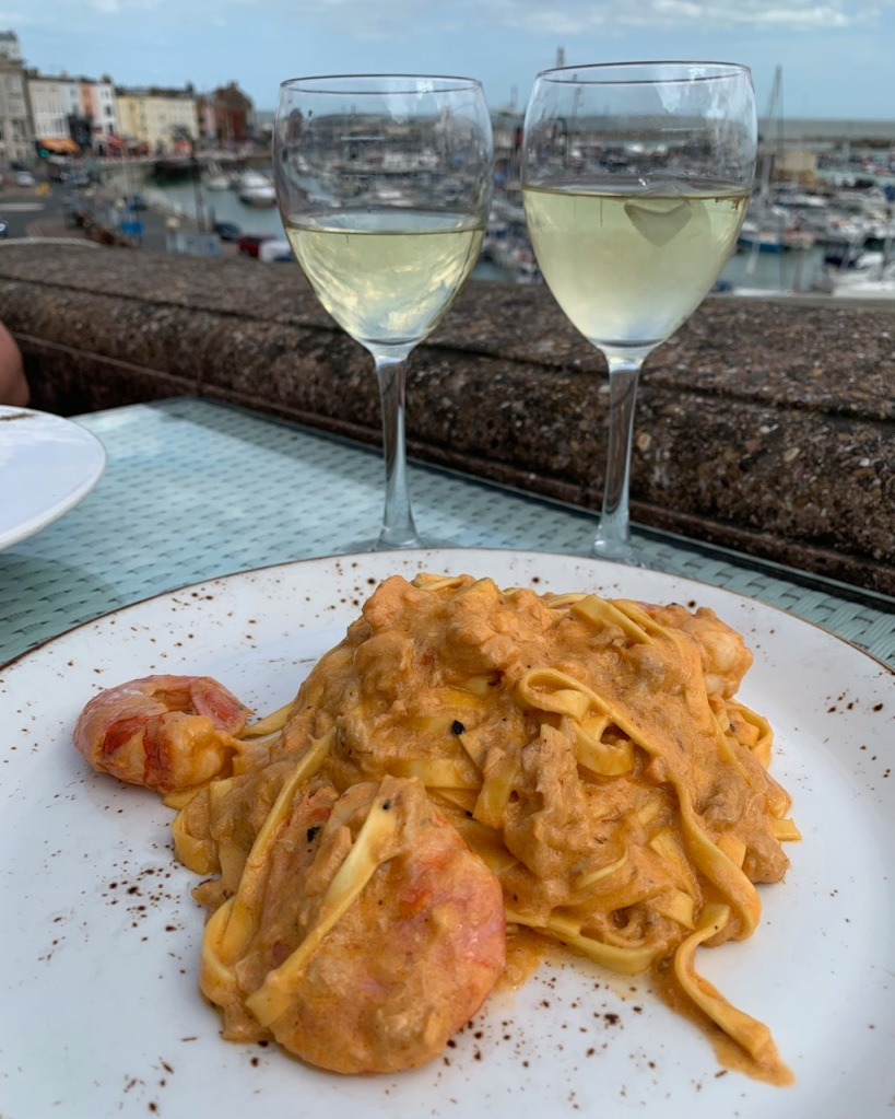 plate with pasta, two glasses of wine and ramsgate marina in the background