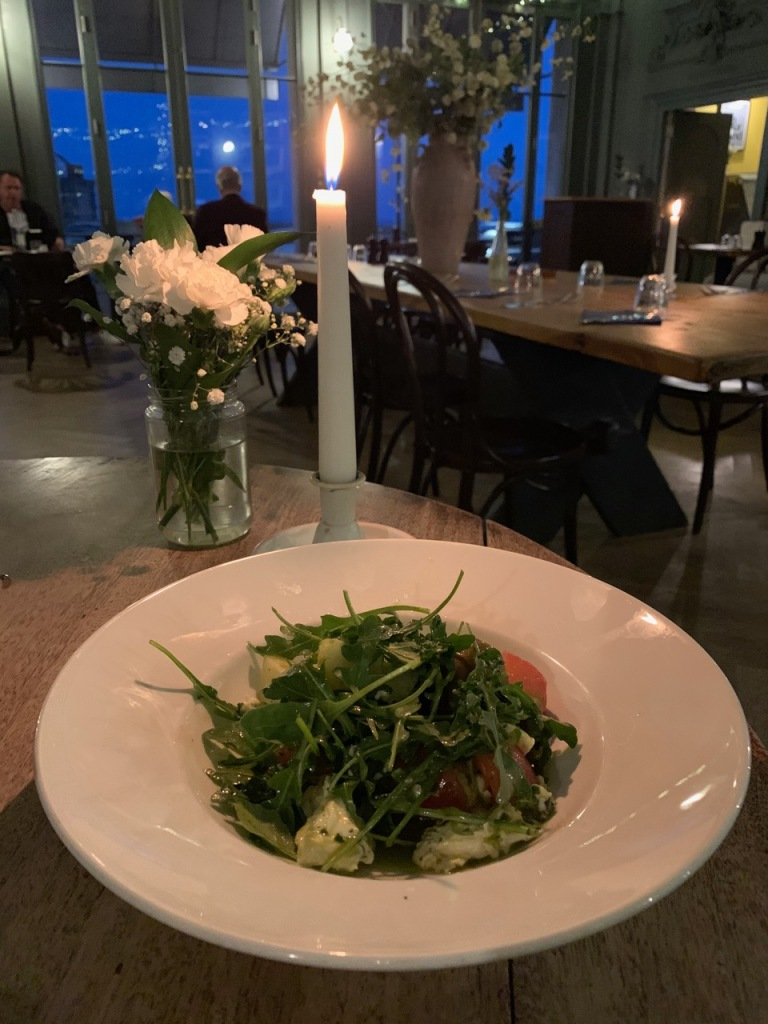 Romantic restaurant photo with candles and flowers in the background, plate of salad in the foreground