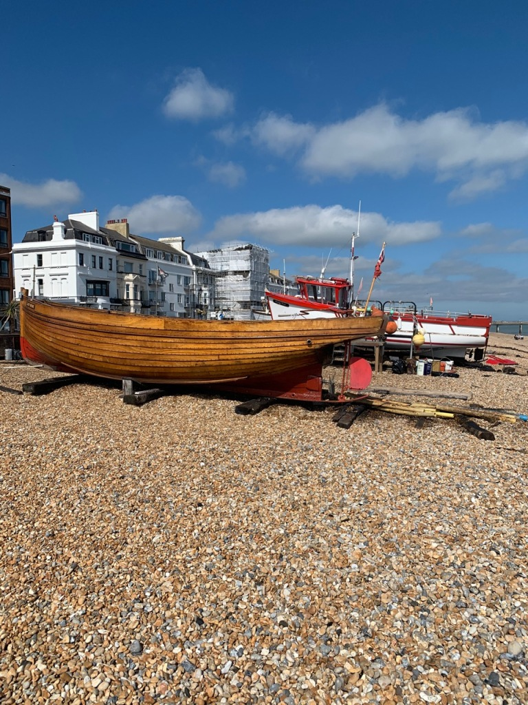 Boat, beach with pebbles, blue skies