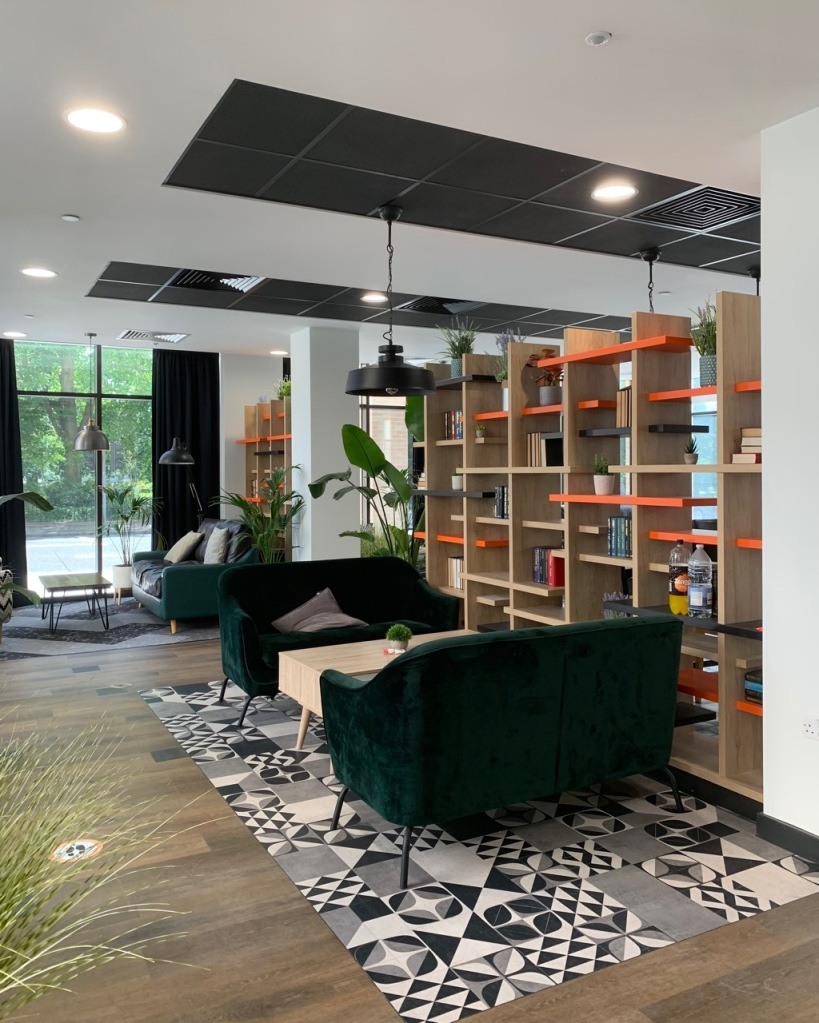 ground floor co working space with sofas and tables, shelves