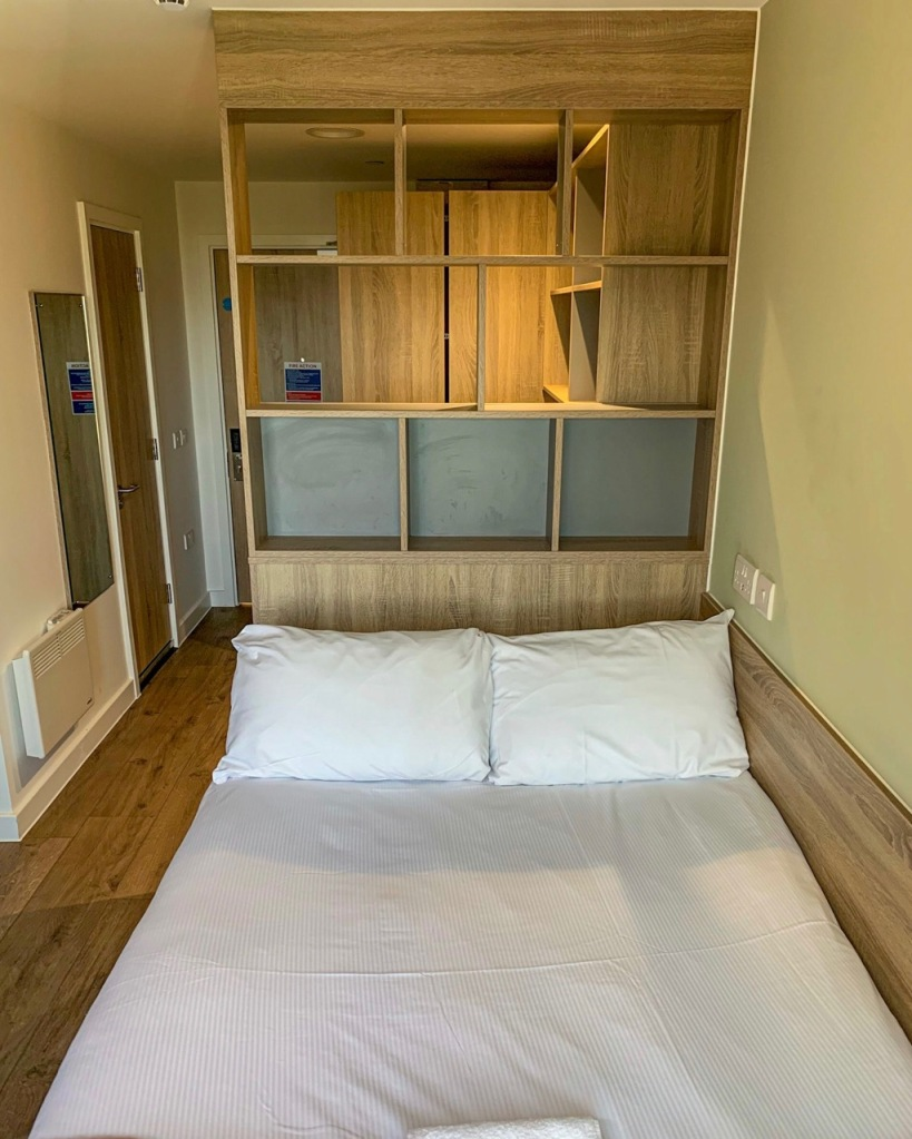 bed with pillows and shelves at the rear